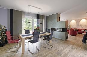 Der gemeinsame Ess- und Wohnbereich ist großzügig und modern gestaltet. Der 15-fach einstellbare Gas-Kamin ist so angebracht, dass man das Feuer im Sitzen gut sieht.