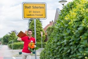 Straßenpreis-Moderator Giuliano vor dem Ortsschild. Er ist persönlich nach Schortens gekommen, um den Gewinnern ihren Scheck zu überreichen. Foto: Postcode Lotterie/Wolfgang Wedel