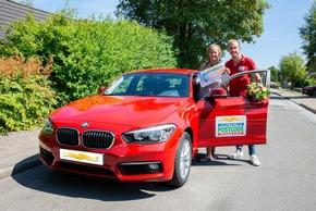 Straßenpreis-Gewinnerin Ronja mit dem 10.000-Scheck und Straßenpreis-Moderator Felix Uhlig neben dem neuen 1er BMW. Foto: Postcode Lotterie/Wolfgang Wedel