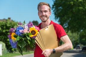 Postcode-Moderator Felix Uhlig auf dem Weg zu den Gewinnerinnen des zweiten Straßenpreises im Mai. Foto: Postcode Lotterie/Wolfgang Wedel