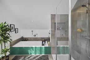 Das Familienbadezimmer lässt keine Wünsche offen: Badewanne, Walk-In-Dusche, WC und Waschbecken in hochwertiger Qualität und Optik.