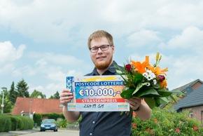 Straßenpreis-Gewinner Marc mit seinem Scheck über 10.000 Euro. Foto: Postcode Lotterie/Wolfgang Wedel