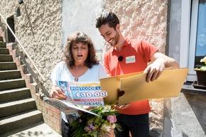 Es bleibt nicht bei zwei Schecks, denn Antje, hier mit Postcode-Moderator Giuliano Lenz, hat drei Lose bei der Deutschen Postcode Lotterie. Foto: Postcode Lotterie/Marco Urban