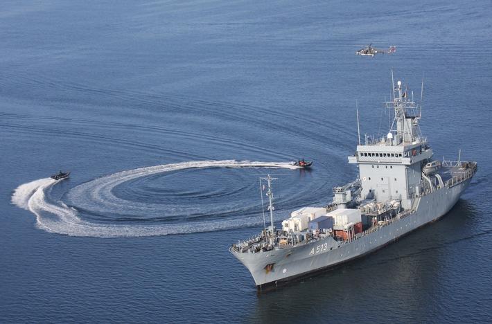 """Simulierter Speedbootangriff auf dem Tender """"Rhein"""". Im Überflug ist der Bordhubschrauber Mk 88A """"Sea Lynx"""" zu sehen."""