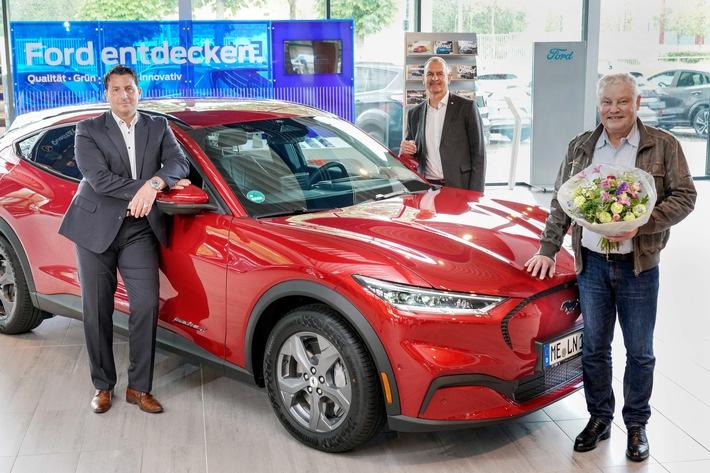 """Strahlende Gesichter in Düsseldorf: Dr. Ludger Terhart ist der erste Kunde in Deutschland, der einen batterie-elektrischen Ford Mustang Mach-E ausgeliefert bekommen hat. Er hatte die Mustang Mach-E-Version mit Heckantrieb und größerer Batterie (""""Extended Range"""") bestellt. Farbe: Lucid-Rot Metallic. Mit dem neuen Mustang Mach-E, einem 5-türigen Crossover-SUV, präsentiert Ford eine rein elektrisch angetriebene Mustang-Variante. Das Bild zeigt Marco Möller (links - Mitglied der Geschäftsführung des Auto-Park Rath in Düsseldorf), Stefan Wieber (Mitte, hinten - Direktor Pkw der Ford-Werke GmbH für Deutschland, Österreich und die Schweiz) sowie Dr. Ludger Terhart (vorne rechts - Mustang Mach-E-Käufer). / Weiterer Text über ots und www.presseportal.de/nr/6955 / Die Verwendung dieses Bildes ist für redaktionelle Zwecke unter Beachtung ggf. genannter Nutzungsbedingungen honorarfrei. Veröffentlichung bitte mit Bildrechte-Hinweis."""