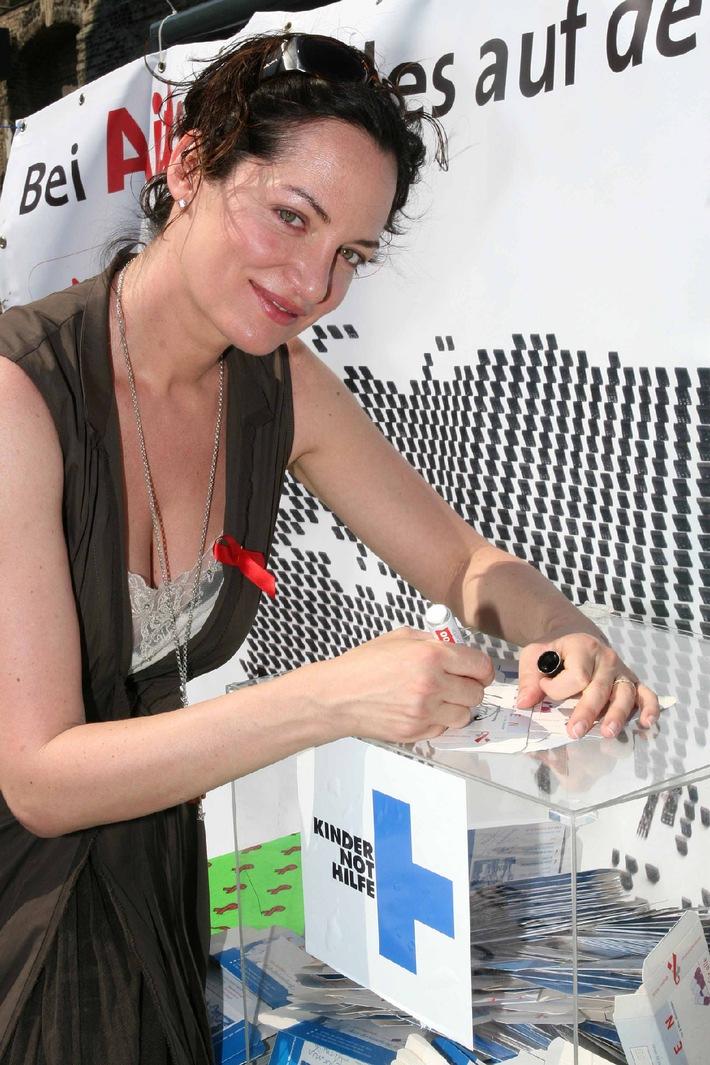 """Kindernothilfe-Botschafterin Natalia Wörner unterschreibt am Mittwoch, 14. Juni, vor der Berliner Gedächtniskirche eine Medikamentenschachtel der Aktion """"Pillen statt Profite"""". Damit macht die Schaupielerin darauf aufmerksam, dass es immer noch keine speziellen Medikamente für HIV-infizierte Kinder gibt. Bundesweit haben sich an der Aktion bereits 450.000 Menschen mit einer Unterschrift beteiligt. Pharma-Unternehmen werden mit der Aktion aufgefordert, neue Medikamente für HIV-infizierte Kinder so schnell wie möglich zu entwickeln und kostengünstig zur Verfügung zu stellen. Foto: Agentur Bildschön. Die Verwendung dieses Bildes ist für redaktionelle Zwecke honorarfrei. Abdruck bitte unter Quellenangabe: """"obs/Kindernothilfe"""""""