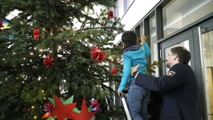 Ein Schüler schmückt den Weihnachtsbaum im Foyer des Polizeipräsidiums.