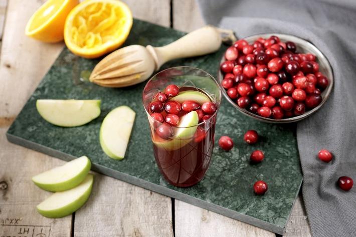 """Weihnachtserfrischung: Passend zum Fest in sattem Rot mit leckeren Apfelscheiben und Cranberries garniert, ist der Drink die geschmackvolle und leichte Erfrischung - ob zu Gebäck, Weihnachtsbraten oder für Zwischendurch. Weiterer Text über ots und www.presseportal.de/nr/7974 / Die Verwendung dieses Bildes ist für redaktionelle Zwecke honorarfrei. Veröffentlichung bitte unter Quellenangabe: """"obs/Coca-Cola Deutschland/Mariella Lahodny"""""""