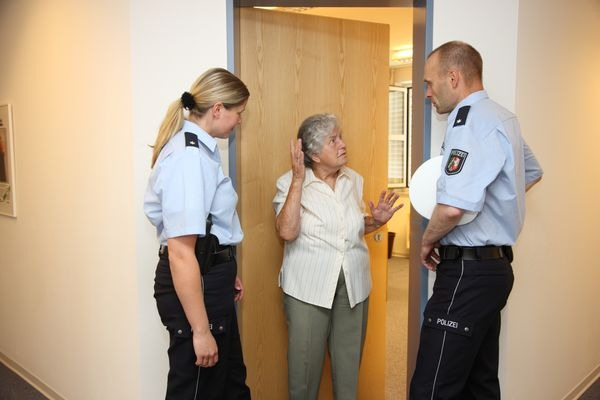 Symbolbild Seniorin mit Polizeibeamten