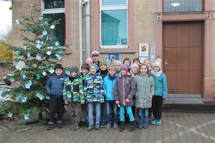 Schüler und Schülerinnen vor dem Weihnachtsbaum