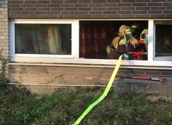 Einsatzkräfte gelangen durch ein Fenster in die Wohnung