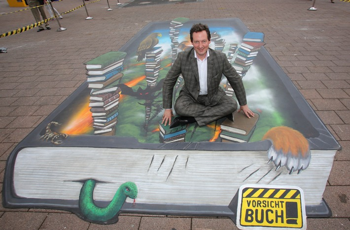"""Zahlreiche prominente Autoren, darunter auch Eckart von Hirschhausen,lassen sich in einem3D Street Art Gemälde buchstäblich in einen Bücherdschungel fallen.""""Vorsicht Buch!"""" ist eine bundesweite Initiative der deutschen Buchbranche, die noch mehr Menschen für Bücher begeistert und den Buchhandel stärkt. Weiterer Text über OTS und www.presseportal.de / Die Verwendung dieses Bildes ist für redaktionelle Zwecke honorarfrei. Veröffentlichung bitte unter Quellenangabe: """"obs/Börsenverein des Dt. Buchhandels e.V."""""""