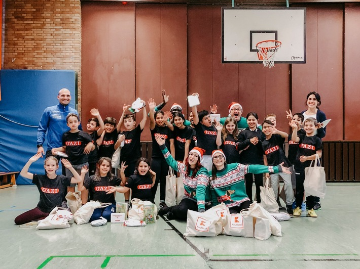 """Kinder des Projekts """"Fußball trifft Kultur"""" in Stuttgart freuen sich über Geschenke von Kaufland, die sie nach einem gemeinsamen Spielenachmittag in der Schulturnhalle erhielten. Foto: Kaufland"""