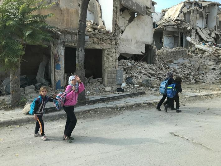 © UNICEF/DT2017-58622/Ninja Charbonneau | Syrien: Kinder sind mit UNICEF-Rucksäcken zwischen den Ruinen von Aleppo unterwegs.