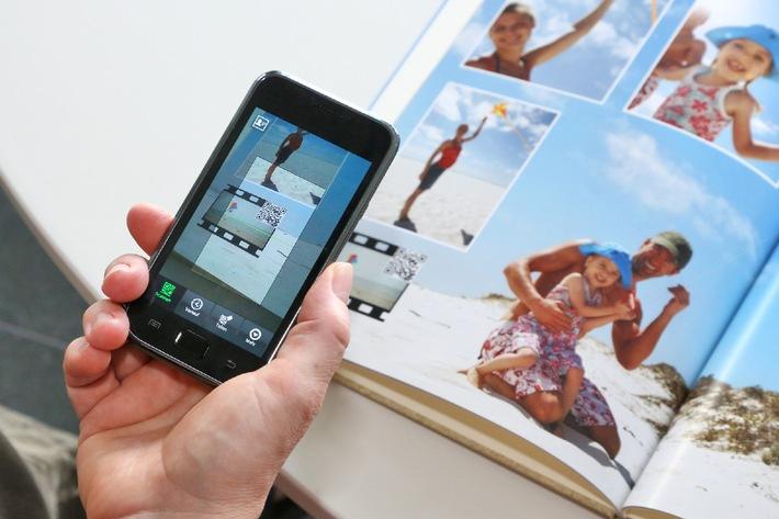 """Neu: Videos ins CEWE FOTOBUCH integrieren - Dank eines innovativen Tools lassen sich jetzt Videos ins CEWE FOTOBUCH integrieren. Sie werden zusammen mit einem QR-Code abgebildet und können mithilfe eines Smartphones oder Tablets jederzeit und überall abgespielt werden. Die Verwendung dieses Bildes ist für redaktionelle Zwecke honorarfrei. Veröffentlichung bitte unter Quellenangabe: """"obs/CeWe Color AG & Co. OHG"""""""