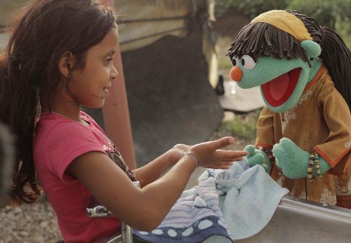 Raya, die Hygiene-Botschafterin der Sesame Street (Sesamstraße), zeigt einem syrischen Mädchen im Libanon das richtige Händewaschen. Foto: World Vision