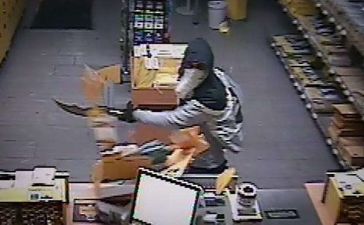 Der Täter schlägt mit seinem Schwert und fordert Bargeld.