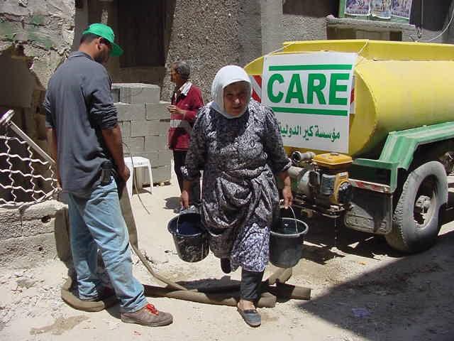 """Verteilung von Wasser in Dschenin - eine alte Frau holt Wasser vom mobilen CARE-Tank im Flüchtlingslager. Die Verwendung dieses Bildes ist für redaktionelle Zwecke honorarfrei.  Abdruck bitte unter Quellenangabe: """"obs/CARE Deutschland"""""""