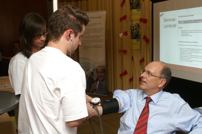 Hessens Sozialminister Stefan Grüttner ließ sich bei der Vorstellung der bpa-Roadshow von einer examinierten Pflegefachkraft Blut abnehmen.
