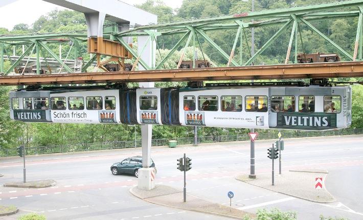 """Der neue Veltins-Mehrwegkasten hoch über den Dächern von Wuppertal - ein Hingucker zum Augenreiben! Immer wieder geht zwischen Vohwinkel und Elberfeld der Blick der Fußgänger gen Himmel, denn der visuell überdimensionierte Veltins-Kasten in Form der Schwebebahn ist ebenso ungewöhnlich wie einmalig. Die Verwendung dieses Bildes ist für redaktionelle Zwecke honorarfrei. Abdruck bitte unter Quellenangabe: """"obs/Brauerei C. & A. Veltins GmbH"""" Weiterer Text über ots und www.presseportal.de"""