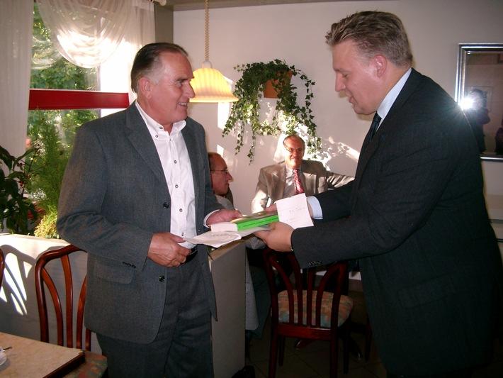 Landrat Wolfgang Spelthahn überreicht Horst Fittje ein Buchgeschenk für die weiteste Anreise