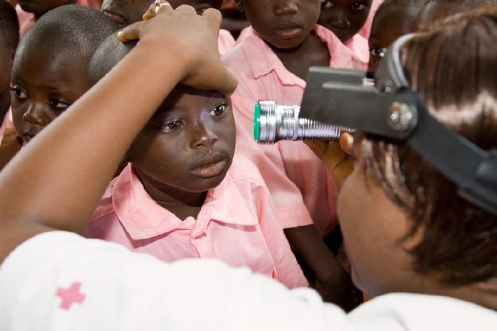 """Früherkennung bei Kindern: In einer Schule in Ghana untersucht eine Augenpflegerin des Roten Kreuzes die Augen eines Mädchens. Weiterer Text über OTS und www.presseportal.ch/pm/100007849 / Die Verwendung dieses Bildes ist für redaktionelle Zwecke honorarfrei. Veröffentlichung bitte unter Quellenangabe: """"OTS.Bild/Schweizerische Zahnärzte-Gesellschaft SSO/© Hilde Eberhard, Uster"""""""