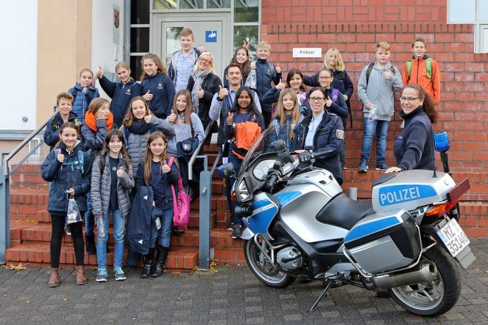 """Die zur Erinnerung an diesen Workshop gefertigte Aufnahme zeigt die 20 Schüler und Schülerinnen des """"Raiffeisen-Campus"""" aus Dernbach und deren Lehrer Herr Moritz Frank. Im Vordergrund von links nach rechts, POK'in Jäger und POK'in Kloy."""