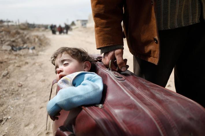 Ein Mann auf der Flucht in Syrien trägt ein Kind in einem Koffer. © UNICEF/UN0185401/Sanadiki