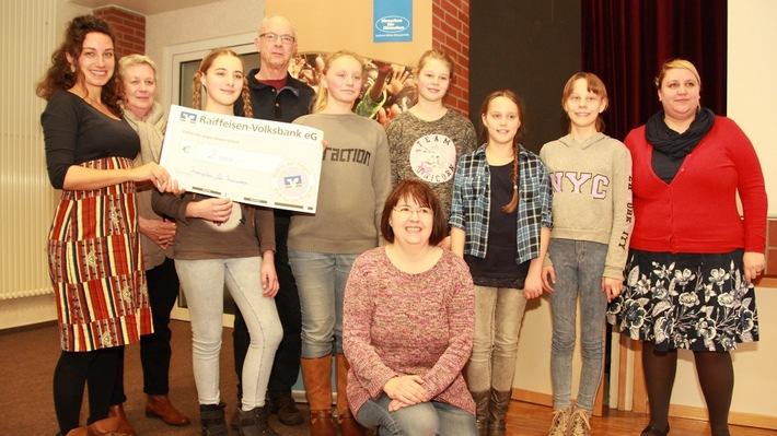 Rosanna Heinz von der Stiftung Menschen für Menschen nimmt den Spendenscheck in Höhe von 2000 Euro von der Charity AG der KGS Wiesmoor entgegen.