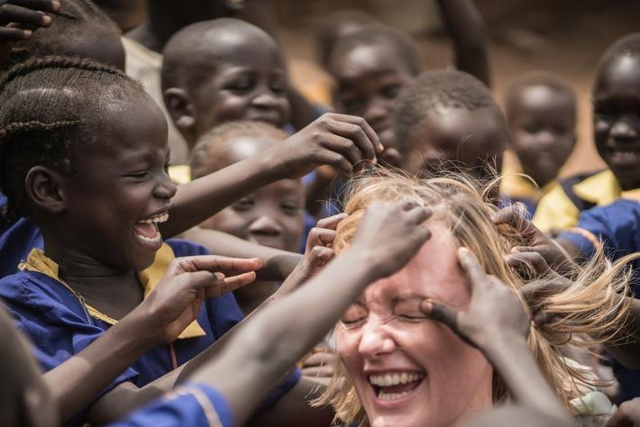 """""""Aktion Deutschland Hilft"""" gewinnt Auszeichnung / Hilfsbündnis erhält dritten Platz beim PR-Bild Award für das beste Foto in der Kategorie NGO / """"In der Mitte"""": Im Südsudan herrscht Hunger, unter dem eine Million Kinder unter fünf Jahren leiden. Die Jungen und Mädchen auf dem Bild erhalten dank der Hilfsorganisation Malteser International, die Mitglied im Bündnis """"Aktion Deutschland Hilft"""" ist, jeden Tag eine warme Mahlzeit in ihrer Schule. Als ein Team des Hilfsbündnisses das Projekt in der Hauptstadt Juba besuchte, stellten die Kinder schnell fest: helle Haut fühlt sich genau an wie ihre - im Gegensatz zu den glatten Haaren der Mitarbeiterin von """"Aktion Deutschland Hilft"""". Weiterer Text über ots und www.presseportal.de/nr/50116 / Die Verwendung dieses Bildes ist für redaktionelle Zwecke honorarfrei. Veröffentlichung bitte unter Quellenangabe: """"obs/Aktion Deutschland Hilft e.V./ADH/Max Kupfer"""""""