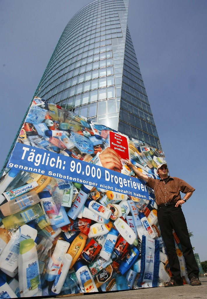 NABU-Bundesgeschäftsführer Leif Miller fordert vor einem 25 Kubikmeter großen Verpackungskubus auf dem Potsdamer Platz die Rote Karte für Recyclingpreller. Für diese Tonne Berliner Verpackungsmüll täglich zahlen die Drogerien keinen Beitrag für die haushaltsnahe Sammlung und die Verbraucher doppelt.