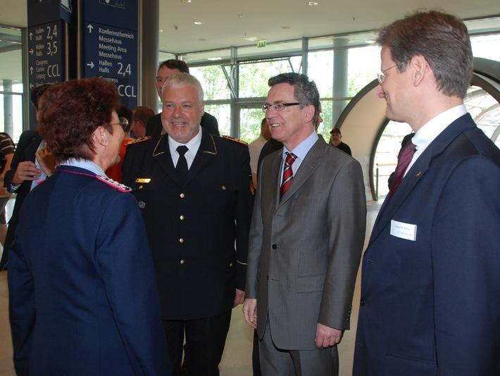 Hans-Peter Kröger, Präsident des DFV und Innenminister Thomas de Maizière begrüßen Ursula Keilholz am Stand des DFV