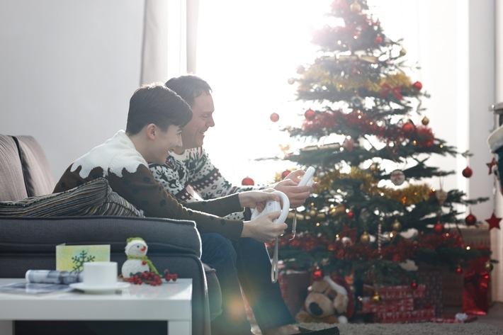 """Vater und Sohn spielen gemeinsam Computer und Videospiele zur Weihnachtszeit / Weiterer Text über ots und www.presseportal.de/nr/64382 / Die Verwendung dieses Bildes ist für redaktionelle Zwecke honorarfrei. Veröffentlichung bitte unter Quellenangabe: """"obs/game - Verband der deutschen Games-Branche/Dean Mitchell"""""""