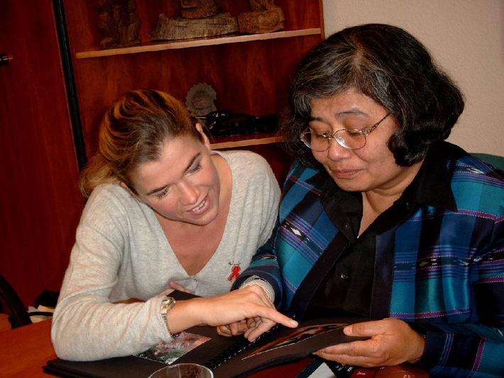 """Anke Engelke und Krisana Kraisintu gucken sich Bilder aus einem Aids-Projekt der action medeor an. Die Verwendung dieses Bildes ist für redaktionelle Zwecke honorarfrei. Abdruck bitte unter Quellenangabe: """"obs/action medeor"""""""