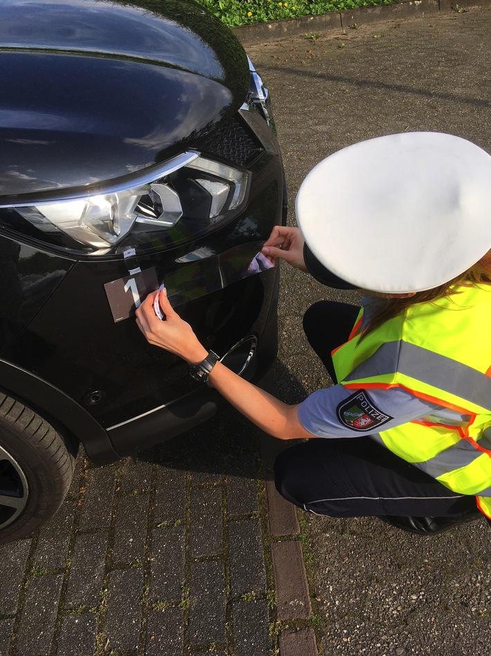 Das Foto zeigt eine Polizistin, die Spuren am Auto nach einer Unfallflucht sichert. (Symbolbild: Polizei Rhein-Kreis Neuss)