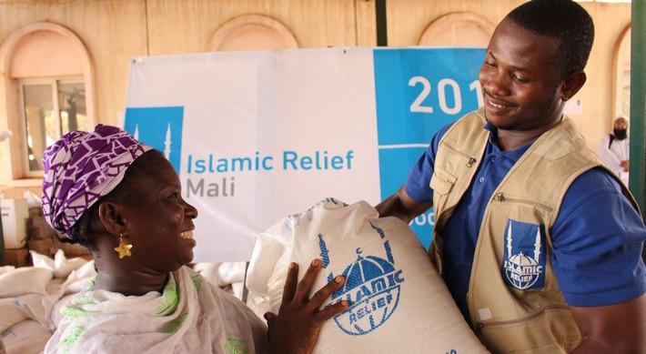 """Ein Sozialarbeiter von Islamic Relief übergibt der alleinerziehenden Nango in Mali ihr Lebensmittelpaket. Weiterer Text über ots und www.presseportal.de/nr/50131 / Die Verwendung dieses Bildes ist für redaktionelle Zwecke honorarfrei. Veröffentlichung bitte unter Quellenangabe: """"obs/Islamic Relief Deutschland e.V./M. GOITA/Islamic Relief"""""""